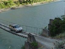 Un jeep conduce sobre un puente de cuerda sobre un río imagenes de archivo