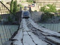 Un jeep conduce sobre un puente de cuerda sobre un río Imagen de archivo