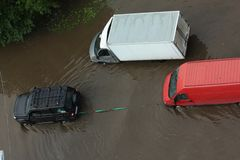 Un jeep del coche que remolca un camión con el motor atascado vía el camino inundado Fotos de archivo libres de regalías