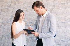 Un jefe del varón firma un documento que le fue traído por una secretaria de la muchacha foto de archivo