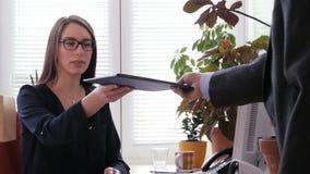 Un jefe masculino da a secretaria de sexo femenino joven un tablero con instrucciones