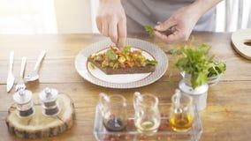 Un jefe masculino está añadiendo el verdor a una ensalada del guisado en un pedazo de un pan negro Foto de archivo