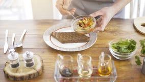 Un jefe masculino está poniendo la ensalada del guisado en un pedazo de un pan negro Foto de archivo