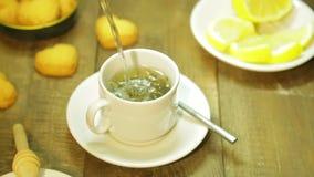 Un jet del agua hirvienda se vierte en una taza de hojas de té almacen de video