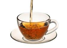 Un jet del té fluye en la taza de té, en el aislamiento Fotografía de archivo
