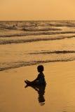 Un jeu de petite fille à la fin de mer de coucher du soleil  Images libres de droits