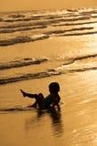 Un jeu de petite fille à la fin de mer de coucher du soleil  Photographie stock
