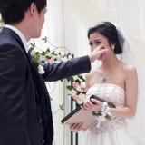 Un jeune échange de couples se voue leur jour du mariage Photographie stock