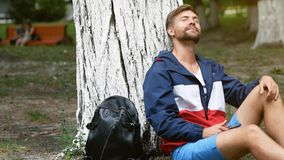 Un jeune étudiant bel détend sous un arbre tandis que tout se déplace Laissez l'attente entière du monde le concept clips vidéos