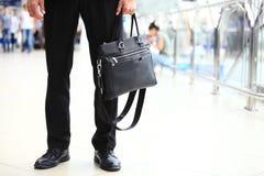 Un jeune étudiant bel d'homme d'affaires dans un costume, vient avec une serviette, à la station, aéroport Concept - un nouveau Images libres de droits