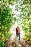 Un jeune ajouter à un chien marchant le long du parc d'automne elle est dans un chandail rouge qu'il est dans le blanc avec un ch Photographie stock libre de droits