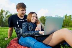 Un jeune ajouter à l'ordinateur portable se reposant en parc Photo stock