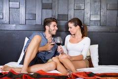 Un jeune ajouter à un verre de vin dans une chambre d'hôtel asiatique de style Images stock