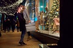 Un jeune ajouter aux paquets fait des emplettes le jour de Noël Image stock