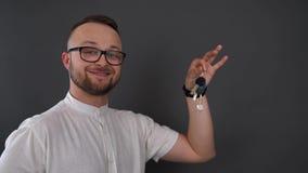 Un jeune, barbu homme avec des verres Clés masculines de prise dans sa main Souriant et secouant des clés banque de vidéos