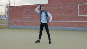 Un jeune, beau, énergique type, un danseur de rue dans le pantalon noir et un gilet bleu avec un capot exécutant un acrobatique banque de vidéos