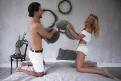 Un jeune beau couple dans le combat blanc avec des oreillers sur le lit moderne dans le grenier conçoit la chambre à coucher, aya photographie stock