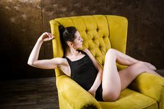 Un jeune beau, femme caucasienne sexy avec le chiffre mince et longues jambes nues, posant nu-pieds reposer sur le fauteuil jaune Images libres de droits