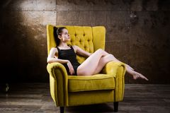 Un jeune beau, femme caucasienne sexy avec le chiffre mince et longues jambes nues, posant nu-pieds reposer sur le fauteuil jaune Image stock