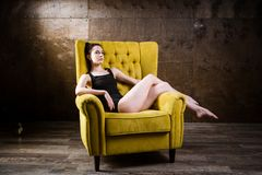 Un jeune beau, femme caucasienne sexy avec le chiffre mince et longues jambes nues, posant nu-pieds reposer sur le fauteuil jaune Photos stock