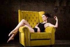 Un jeune beau, femme caucasienne sexy avec le chiffre mince et longues jambes nues, posant nu-pieds reposer sur le fauteuil jaune Photographie stock