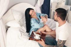 Un jeune, beau jeune homme a apporté les croissants et le café pour le petit déjeuner dans le lit à sa fille aimée photographie stock