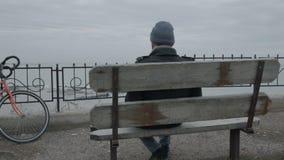Un jeune célibataire s'asseyant sur un banc clips vidéos