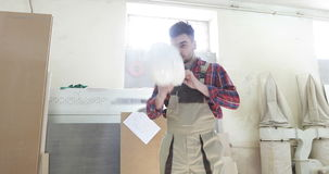 Un jeune charpentier dans l'uniforme de menuiserie mettant sur un casque blanc sur la tête à la production de travail du bois clips vidéos