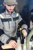 Un jeune charpentier installe un objet en bois dans une machine de scier circulaire Atelier à la maison Homme d'affaires de novic image stock