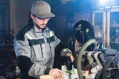 Un jeune charpentier installe un objet en bois dans une machine de scier circulaire Atelier à la maison Homme d'affaires de novic photographie stock libre de droits