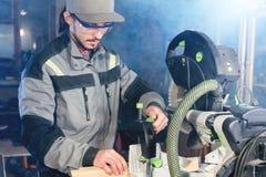 Un jeune charpentier installe un objet en bois dans une machine de scier circulaire Atelier à la maison Homme d'affaires de novic photographie stock