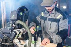 Un jeune charpentier installe un objet en bois dans une machine de scier circulaire Atelier à la maison Homme d'affaires de novic images stock