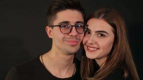 Un jeune couple affectueux embrasse sur un fond noir Portrait banque de vidéos