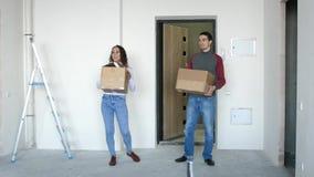 Un jeune couple attrayant entrant dans une nouvelle maison avec des boîtes Un couple joyeux est ?treignant et se tenant sur le se banque de vidéos