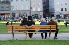Un jeune couple au milieu d'un banc met leurs bras autour de l'un l'autre et un vieux couple au bord du banc image stock