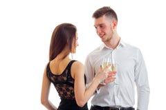 Un jeune couple avec du charme se tient vis-à-vis de l'un l'autre souriant et tenant des verres de vin Images stock