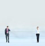 Un jeune couple d'affaires marchant avec des téléphones Images libres de droits
