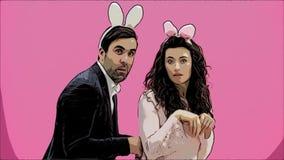 Un jeune couple d'amants apparaît sur le fond rose, reproduisant des chevaux des lièvres Avec les oreilles d'un lapin rose sur clips vidéos