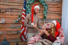 Un jeune couple dans des chapeaux de Santa, à la maison, tenant des verres avec le champagne dans leurs mains Photo libre de droits