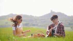 Un jeune couple dans des vêtements lumineux se reposant sur un pré vert clair et ayant un pique-nique - un homme jouant la guitar banque de vidéos