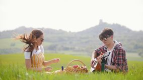 Un jeune couple dans des vêtements lumineux se reposant sur un pré vert clair et ayant un pique-nique - un homme jouant la guitar clips vidéos