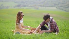 Un jeune couple dans des vêtements lumineux se reposant sur un pré vert clair et regardant ce qui est dans le pottle banque de vidéos