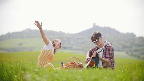 Un jeune couple dans des vêtements lumineux se reposant sur un pré vert clair - un homme jouant la guitare tandis que son amie he clips vidéos