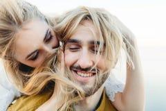Un jeune couple dans l'amour ayant l'amusement et jouant avec des cheveux de la fille Des jeunes mariés gais riant, plan rapproch Photographie stock