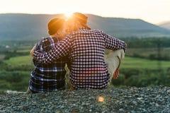 Un jeune couple dans l'amour est penchement posé les uns contre les autres sur le dessus de la montagne au coucher du soleil Cou images libres de droits