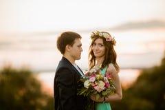 Un jeune couple dans l'amour extérieur au coucher du soleil Image libre de droits