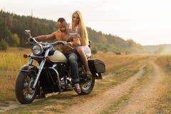 Un jeune couple dans l'amour sur une moto dans le domaine Photographie stock