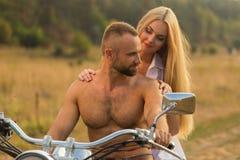 Un jeune couple dans l'amour sur une moto dans le domaine Image libre de droits