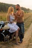Un jeune couple dans l'amour sur une moto dans le domaine Photos libres de droits