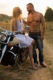 Un jeune couple dans l'amour sur une moto dans le domaine Photographie stock libre de droits